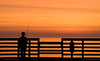 Boy fishing off a pier during sunrise